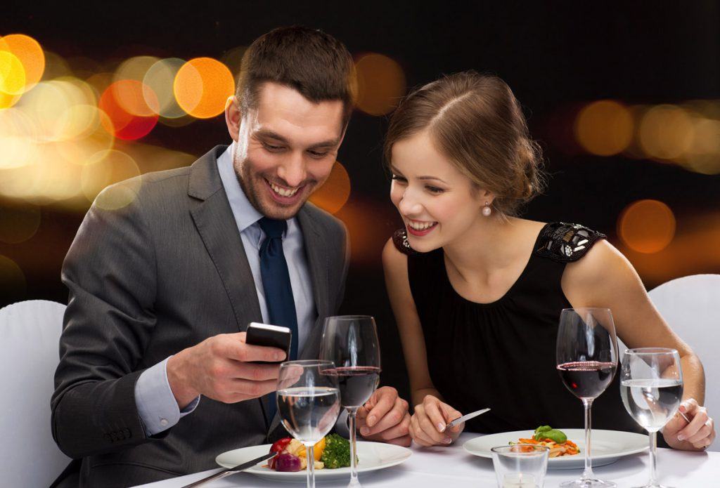 Pareja mirando el móvil en un restaurante mientras cenan